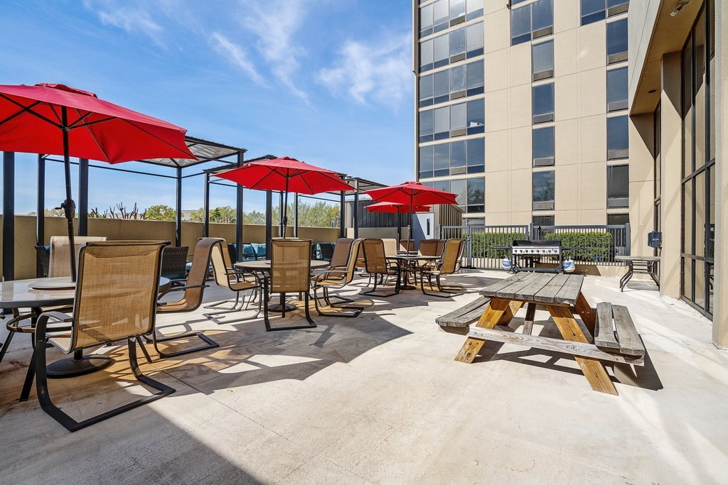 Central Plaza Student Housing outside patio tables and red umbrellas